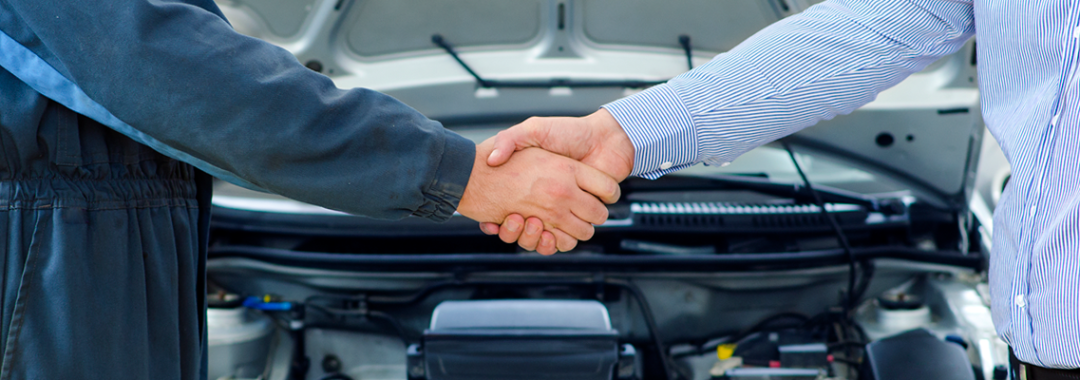 mechanic and customer shaking hands in front of a car engine